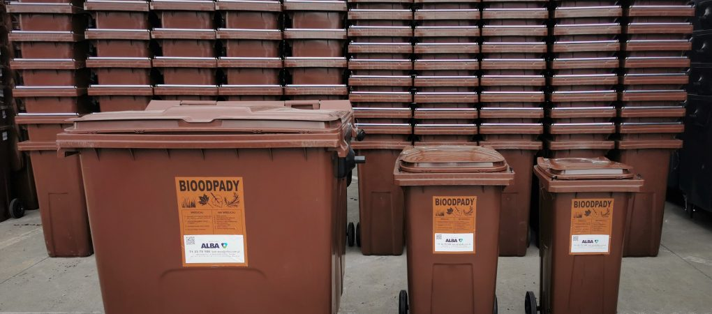 Stos brązowych pojemników na odpady bio. Pojemniki w trzech różnych wielkościach.